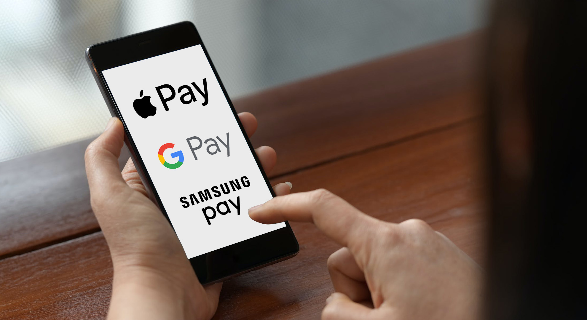 Apple Pay, Samsung Pay, and Google Pay logos on cell phone