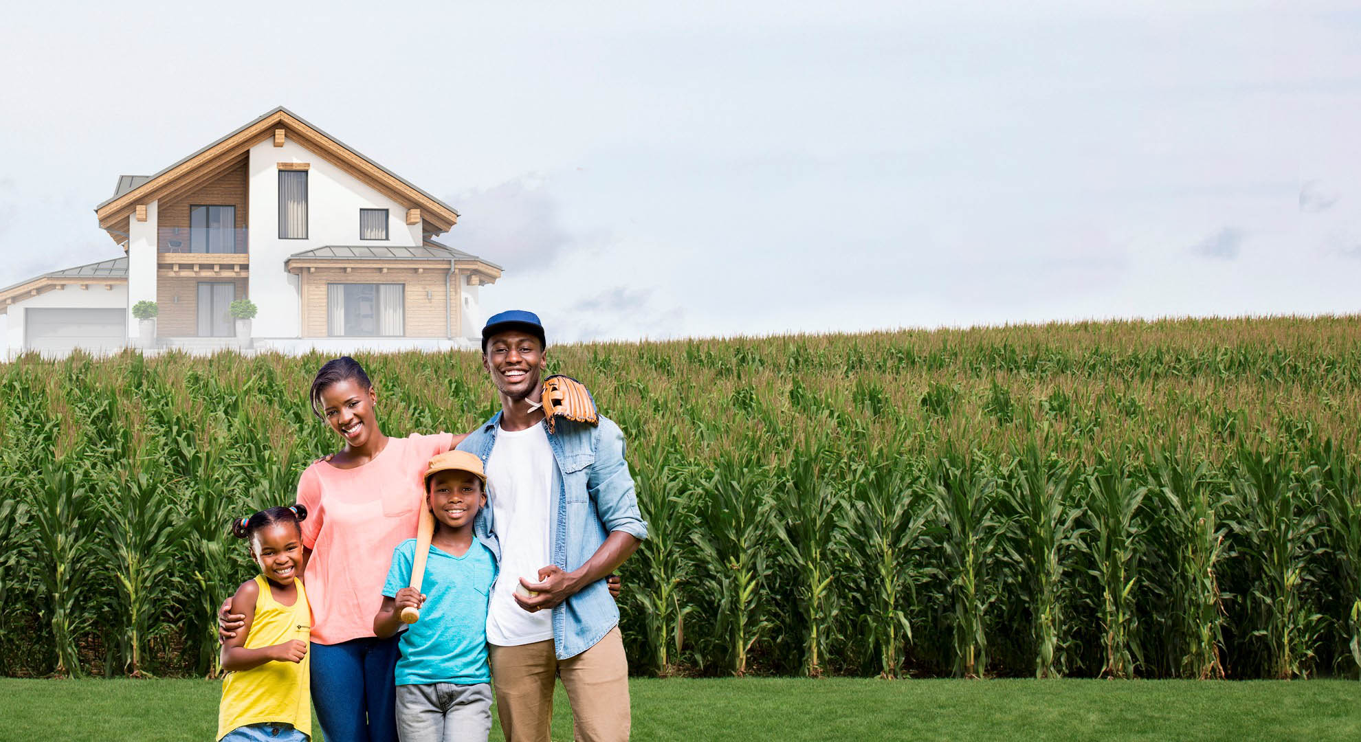 Family standing in corn field with baseball equipment with newly built home in the background