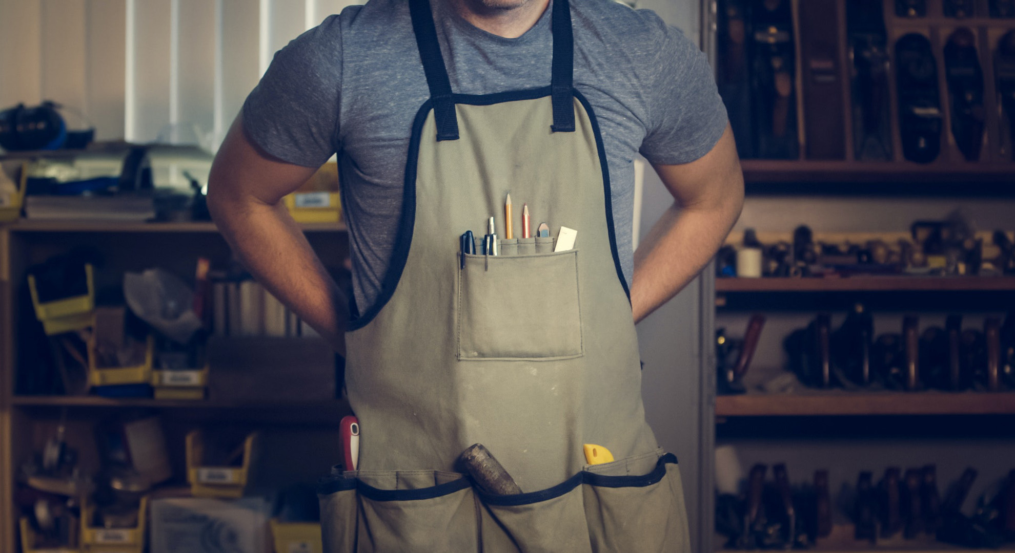 Handyman with apron filled with tools